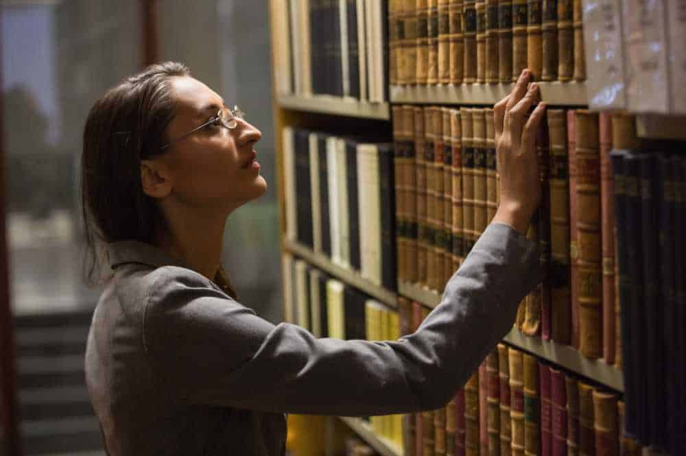 Law student in the law library. Obviously, her application including the law school personal statement was accepted.